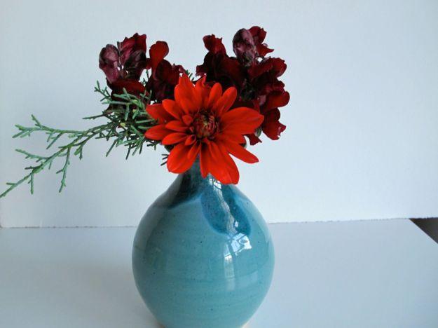 Turquoise vase of Dahlia x hybrida and Antirrhinum majus (Snapdragon)